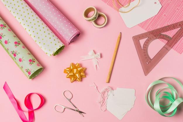 Hohe winkelsicht von briefpapierversorgungen mit geschenkverpackung und tags auf rosa hintergrund Kostenlose Fotos
