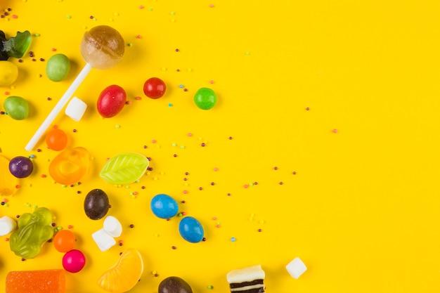 Hohe winkelsicht von bunten süßigkeiten und von lutschern auf gelbem hintergrund Kostenlose Fotos