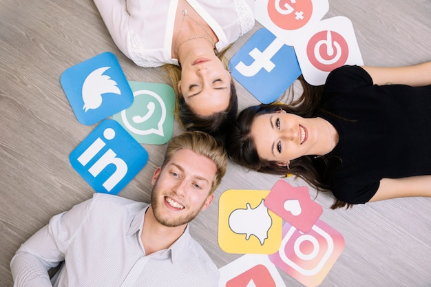 Hohe winkelsicht von den freunden, die auf bretterboden mit social media-ikonen liegen Kostenlose Fotos
