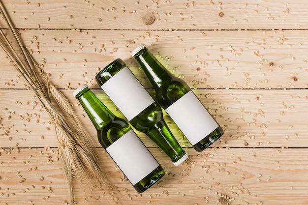 Hohe winkelsicht von drei bierflaschen und ähren auf woodgrain Kostenlose Fotos