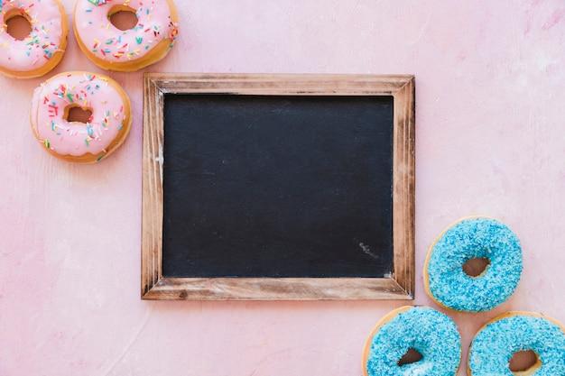 Hohe winkelsicht von frischen schaumgummiringen mit leerem schwarzem schiefer auf rosa hintergrund Kostenlose Fotos