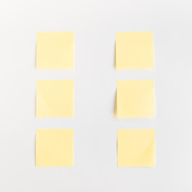 Hohe winkelsicht von gelben klebenden anmerkungen vereinbarte in folge auf weißem hintergrund Kostenlose Fotos