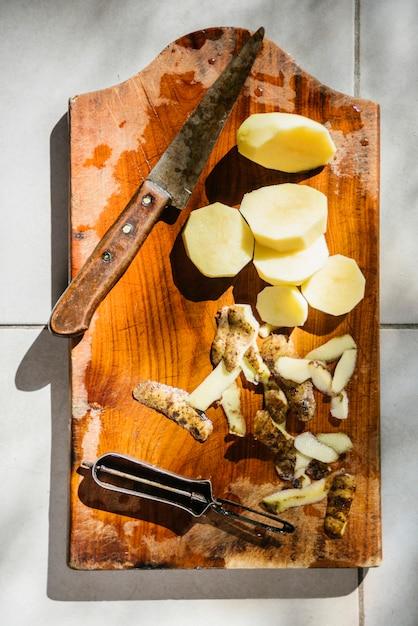 Hohe winkelsicht von geschnittenen kartoffeln mit messer auf hölzernem schneidebrett Kostenlose Fotos