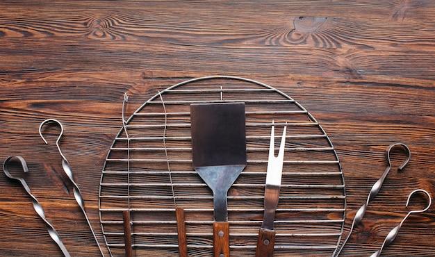 Hohe winkelsicht von grillwerkzeugen auf hölzernem schreibtisch Kostenlose Fotos