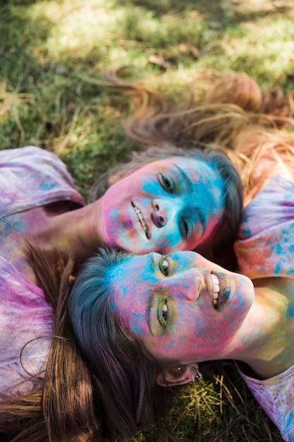 Hohe winkelsicht von jungen frauen mit holi farbe auf ihrem gesicht, das auf dem rasen betrachtet kamera liegt Kostenlose Fotos