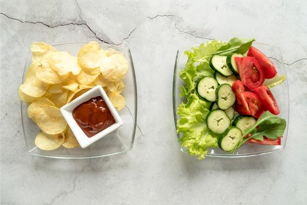 Hohe winkelsicht von kartoffelchips mit soßen- und gemüsesalat auf glasschüssel Kostenlose Fotos