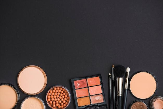Hohe winkelsicht von kosmetischen produkten auf schwarzer oberfläche Kostenlose Fotos