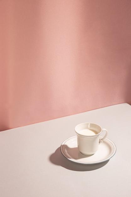 Hohe winkelsicht von milch in der schale gegen rosa hintergrund Kostenlose Fotos