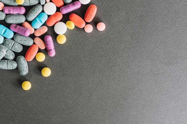 Hohe winkelsicht von verschiedenen bunten pillen auf grauem hintergrund Kostenlose Fotos