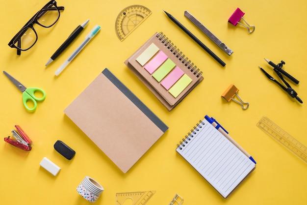 Hohe winkelsicht von verschiedenen schreibwaren auf gelber oberfläche Kostenlose Fotos