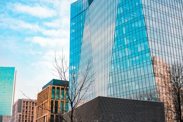 Hohe wolkenkratzer und niedrige gebäude mit glasfenstern in der stadt. geschäftszentrum Premium Fotos