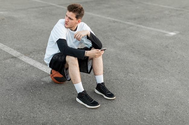 Hoher ansichtmann, der auf einem basketball sitzt Kostenlose Fotos