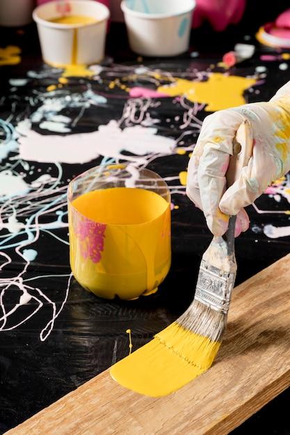 Hoher handwinkel mit handschuhmalerei mit pinsel Kostenlose Fotos