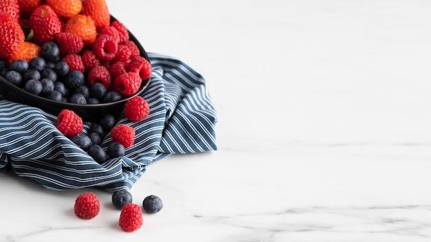 Hoher schüsselwinkel mit erdbeeren, himbeeren und blaubeeren Kostenlose Fotos