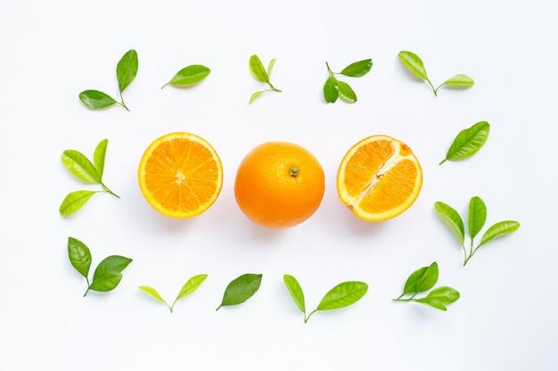Hoher vitamin c-gehalt, saftig und süß. frische orange frucht mit grünblättern auf weiß. Premium Fotos