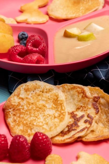 Hoher winkel der babynahrung mit himbeeren und pfannkuchen Kostenlose Fotos