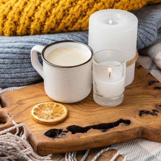 Hoher winkel der brennenden kerzen mit pullover und tasse kaffee Kostenlose Fotos