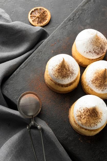 Hoher winkel der desserts auf schiefer mit kakaopulver und sieb Kostenlose Fotos
