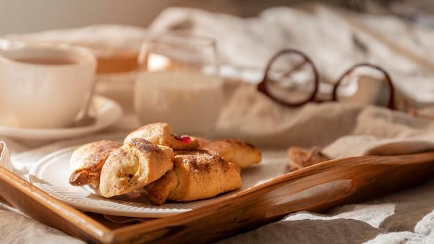 Hoher winkel der desserts auf tablett mit tee und gläsern Kostenlose Fotos