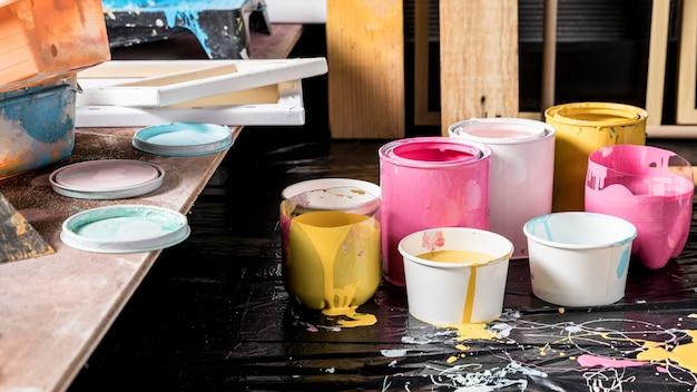 Hoher winkel der farbdosen im studio mit leinwand Kostenlose Fotos