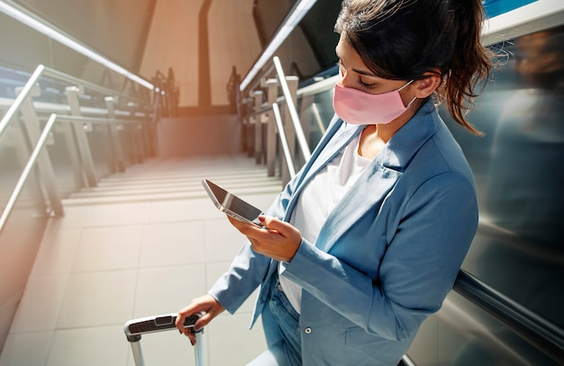 Hoher winkel der frau mit medizinischer maske und gepäck unter verwendung des smartphones am flughafen während der pandemie Kostenlose Fotos