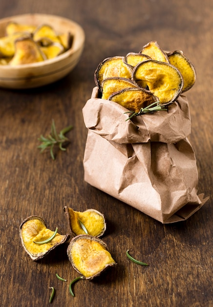Hoher winkel der kartoffelchips in papiertüte mit rosmarin Kostenlose Fotos