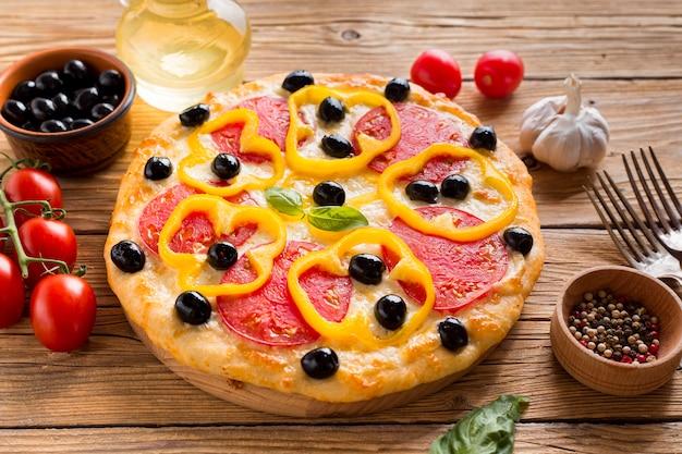 Hoher winkel der köstlichen pizza auf holztisch Kostenlose Fotos