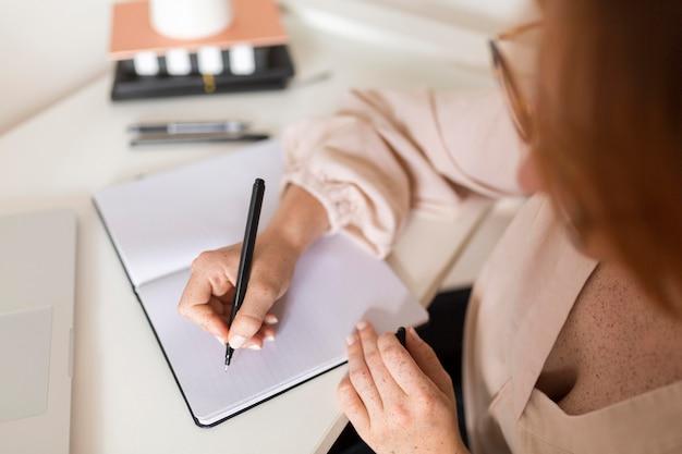 Hoher winkel der lehrerin am schreibtisch während des online-unterrichts Kostenlose Fotos