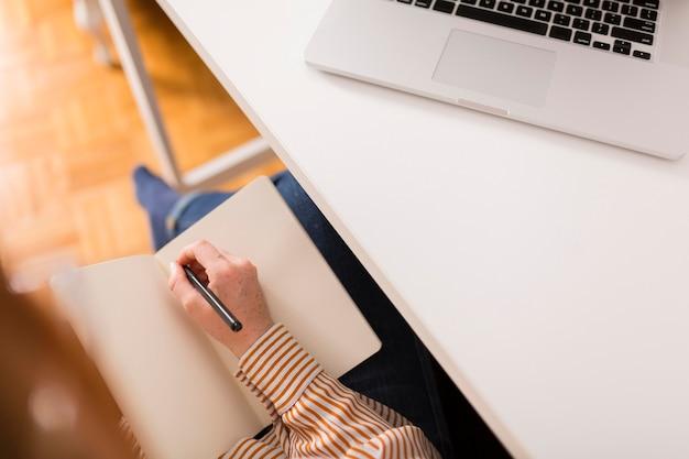 Hoher winkel der lehrerin, die während des online-unterrichts etwas in die tagesordnung schreibt Premium Fotos