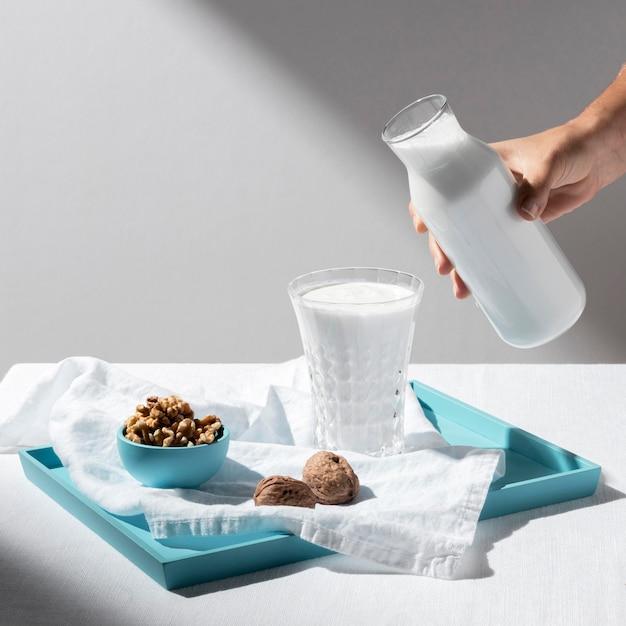 Hoher winkel der person, die milch in volles glas mit walnüssen auf tablett gießt Kostenlose Fotos