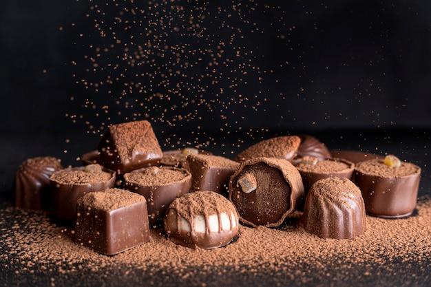 Hoher winkel der praline mit kakaopulver Kostenlose Fotos