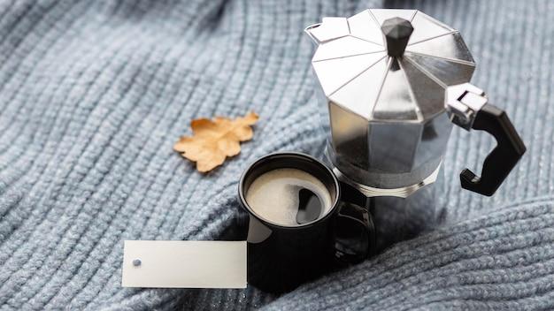 Hoher winkel der tasse kaffee mit wasserkocher auf pullover Kostenlose Fotos