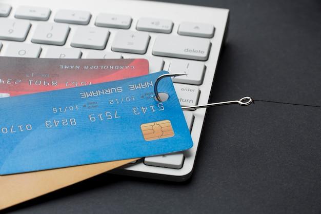 Hoher winkel der tastatur mit kreditkarten und haken für phishing Kostenlose Fotos