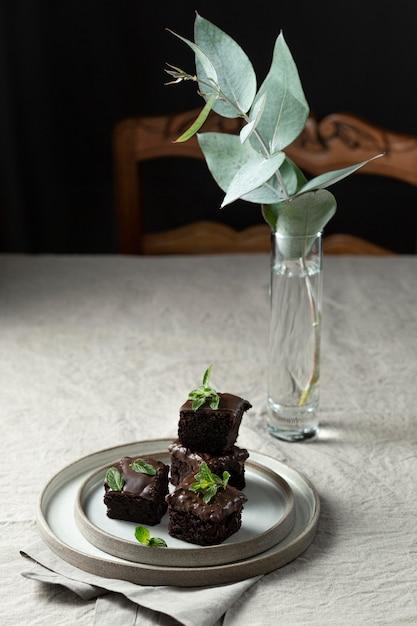 Hoher winkel des desserts auf teller mit pflanze und vase Kostenlose Fotos