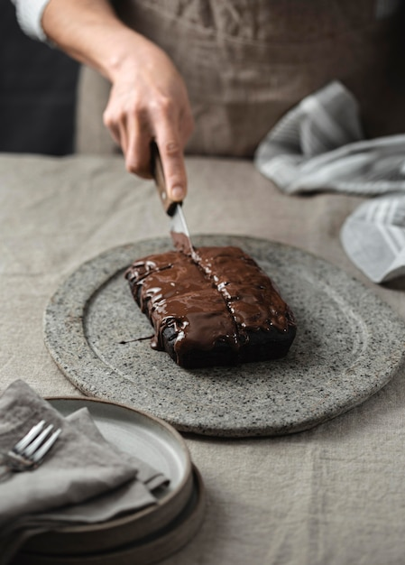 Hoher winkel des konditoren, der in schokoladenkuchen schneidet Kostenlose Fotos