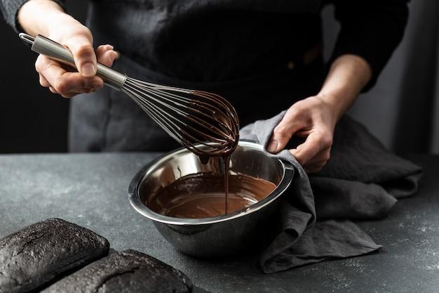 Hoher winkel des konditoren, der schokoladenkuchen vorbereitet Premium Fotos