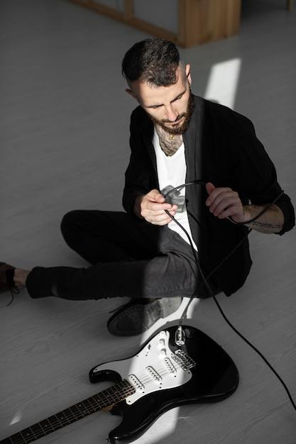 Hoher winkel des männlichen künstlers, der e-gitarre spielt Kostenlose Fotos