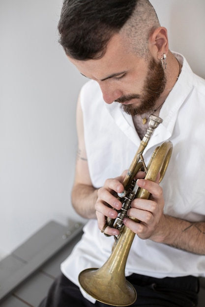 Hoher winkel des männlichen musikers, der kornett spielt Kostenlose Fotos
