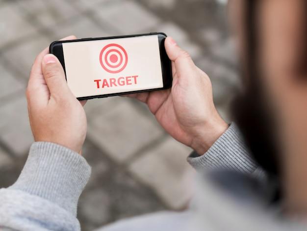 Hoher winkel des mannes, der smartphone mit ziel hält Kostenlose Fotos
