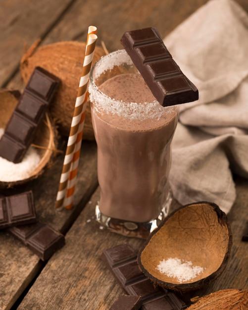 Hoher winkel des milchshake-glases auf tablett mit schokoladenkokosnuss Kostenlose Fotos