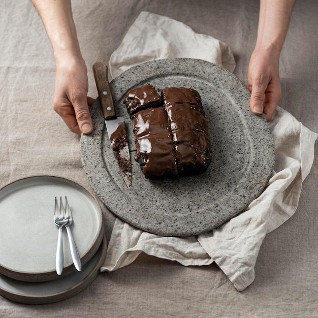 Hoher winkel des schokoladenkuchens auf teller, der vom konditor gehalten wird Kostenlose Fotos