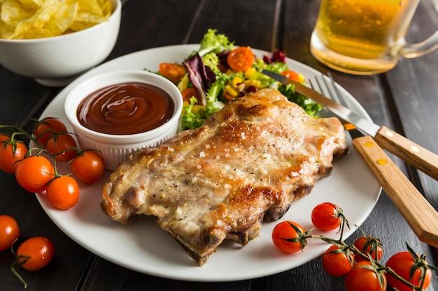 Hoher winkel des steaks auf teller mit bier und salat Kostenlose Fotos