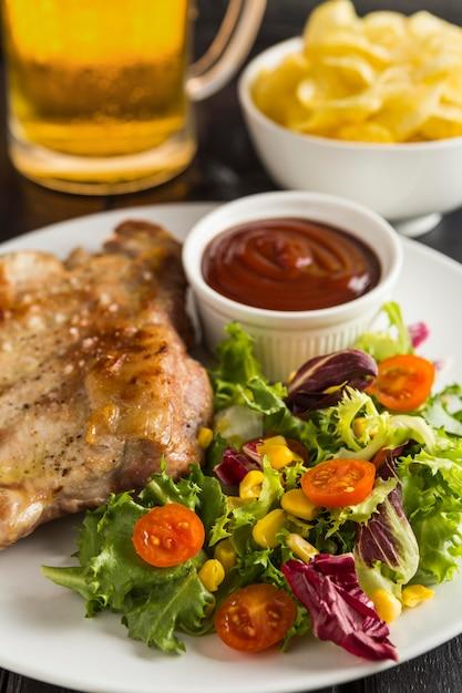 Hoher winkel des steaks auf teller mit salat und bier Kostenlose Fotos