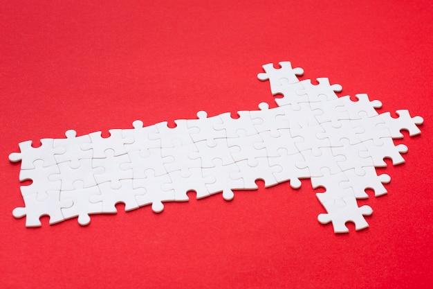 Hoher winkel des weißen pfeils aus puzzleteilen Kostenlose Fotos