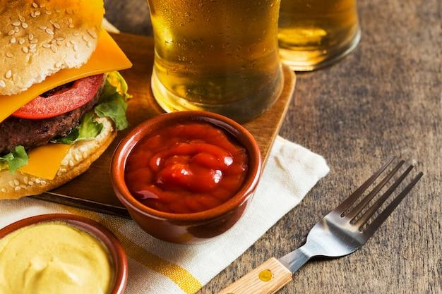 Hoher winkel von gläsern bier mit cheeseburger und sauce Kostenlose Fotos