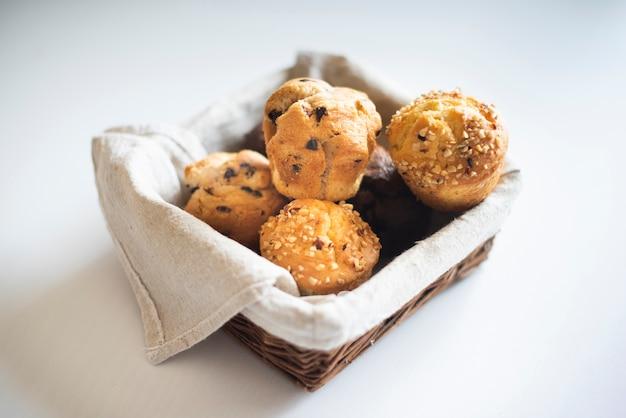 Hoher winkel von muffins im korb auf einfachem hintergrund Kostenlose Fotos