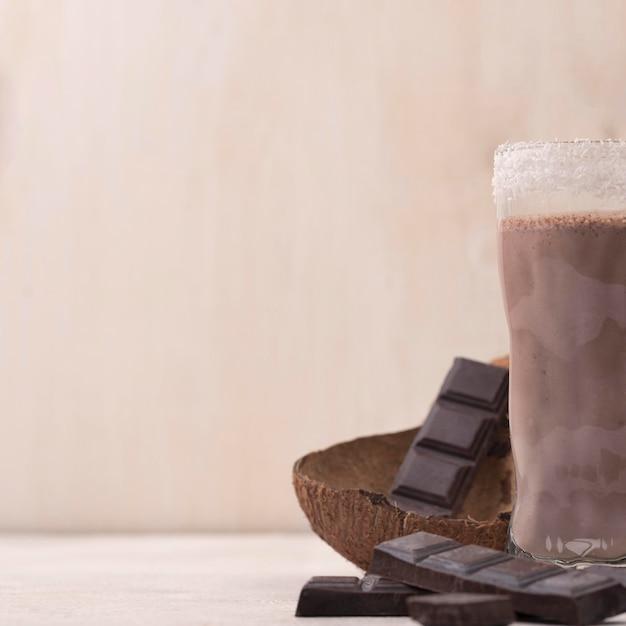Hoher winkel von schokoladenmilchshake-glas mit kopierraum und kokosnuss Kostenlose Fotos