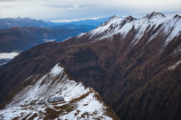 Hoher winkelschuss eines gebäudes auf einem schneebedeckten berg unter einem bewölkten himmel Kostenlose Fotos