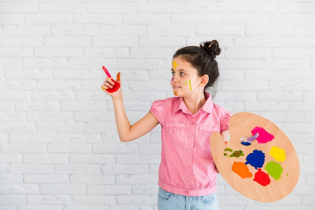 Holdingpalette des kleinen mädchens, die etwas mit dem gemalten roten finger zeigt Kostenlose Fotos
