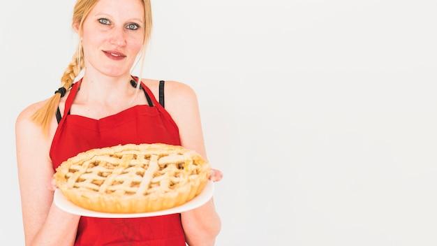 Holdingplatte der blonden frau mit apfelkuchen Kostenlose Fotos